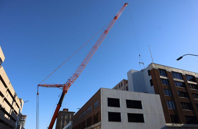 NGC crane placing 12000 lb new HVAC units on Atrium roof